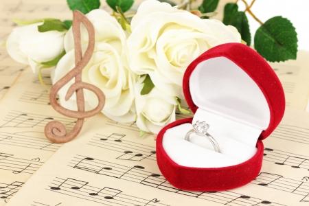 歌: 高音部記号、バラ、音楽的な背景に結婚指輪を持ってボックス