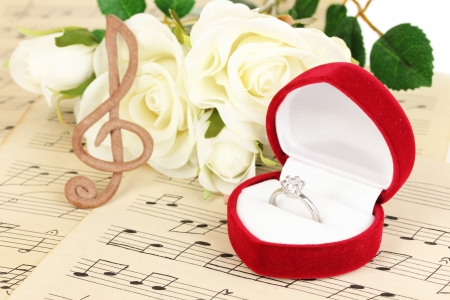 song: Treble clef, roses and box holding wedding ring on musical background Stock Photo
