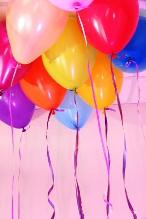 Many bright balloons under ceiling close-up photo