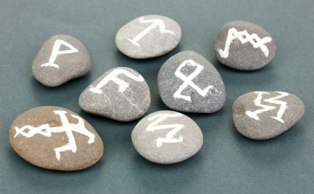 Fortune telling  with symbols on stones on grey background photo