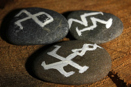 Fortune telling  with symbols on stones on wooden background photo