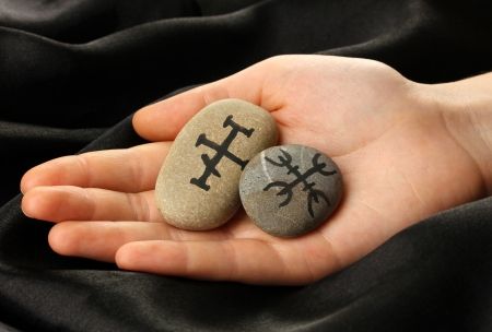 Fortune telling  with symbols on stone in hand on black fabric background Stock Photo - 19100853