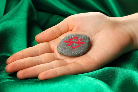 Fortune telling  with symbols on stone in hand on green fabric background Stock Photo - 19100919