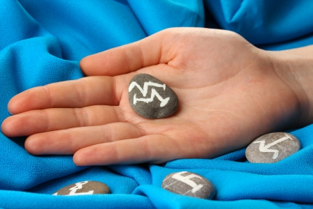 Fortune telling  with symbols on stone in hand on blue fabric background Stock Photo - 19100882