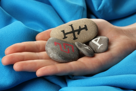Fortune telling  with symbols on stone in hand on blue fabric background Stock Photo - 19100923