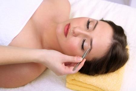 tweezing eyebrow: Beautiful young woman in cosmetic salon close up