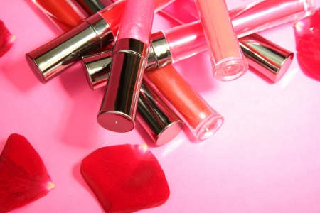 glosses: beautiful lip glosses with rose petals, on pink background Stock Photo