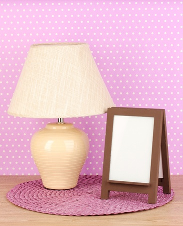 Brown photo frame and lamp on wooden table on lilac wall background Stock Photo - 19145381