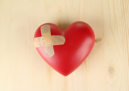 Heart with plaster, on wooden background photo