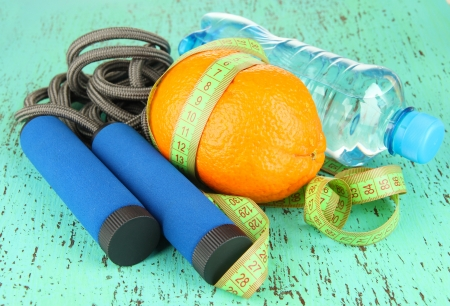 Orange with measuring tape,skipping rope and bottle of water, on color wooden background photo
