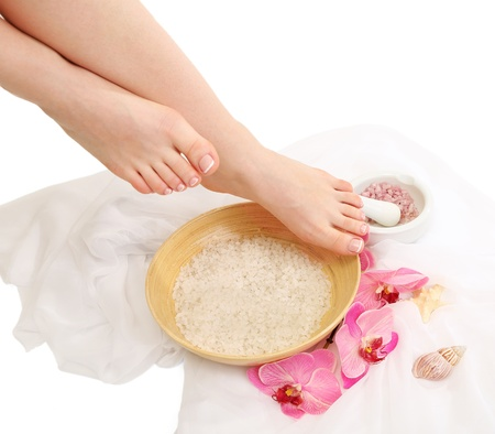 Female feet in spa bowl with sea salt, isolated on white photo