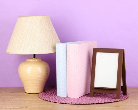 Brown photo frame and lamp on wooden table on lilac wall background photo