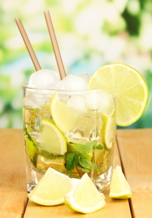 Glass of cocktail with lime and mint on wooden table on bright background photo