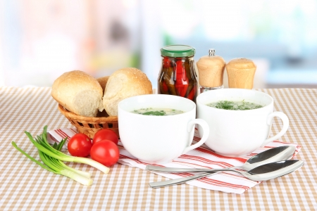 Fragrant soup in cups on table in kitchen photo