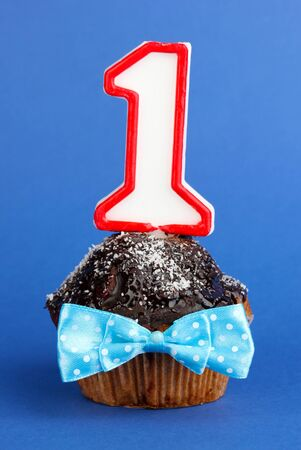 Birthday cupcake with chocolate frosting on blue background photo