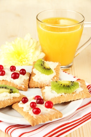 Tasty canapes with cheese and kiwi, cranberry, on color plate, on wooden background photo