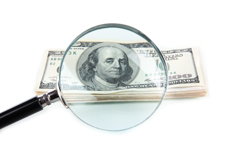 counterfeiting: Hundred dollar bill and magnifying glass isolated on white
