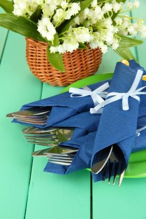 Fork and knife wrapped in blue paper napkin, on color wooden background photo