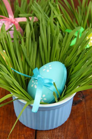 Easter eggs in bowl with grass on wooden table close up photo