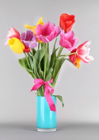 Beautiful tulips in bouquet on gray background photo