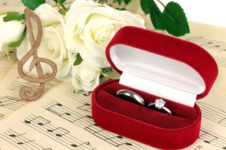 Treble clef, roses and box holding wedding rings on musical background photo