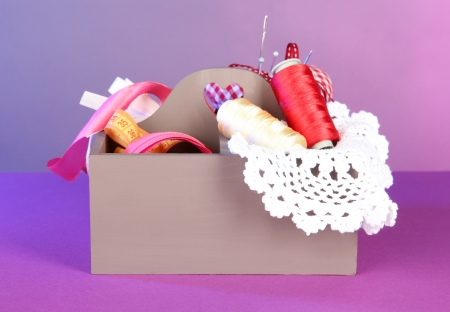 Box with the materials at hand sewing on a color background photo