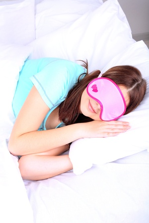 Beautiful young woman sleeping in bed with eye mask photo