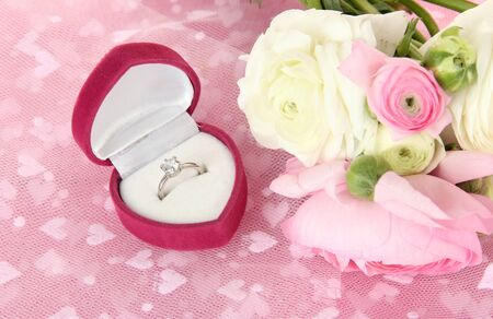 Ranunculus (persian buttercups) and engagement ring, on pink cloth photo