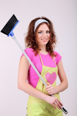Young housewife with broom on grey background photo