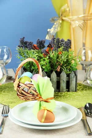 Easter table setting on color background photo