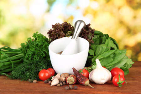 Composition of mortar, spices, tomatoes and  green herbs, on bright background photo