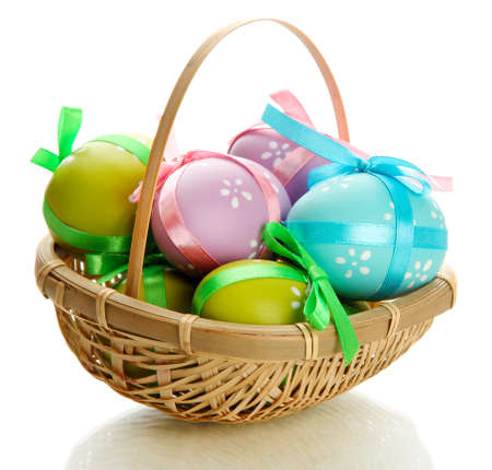 easter basket: Bright easter eggs with bows in basket, isolated on white