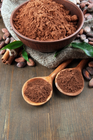 Cocoa powder and cocoa beans  on wooden background photo