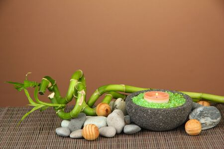 Still life with green bamboo plant and stones, on bamboo mat on color background photo