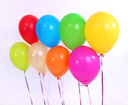Many bright balloons isolated on white photo