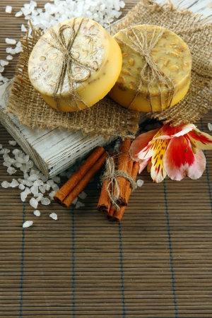 Hand-made soap and sea salt  on grey bamboo mat photo