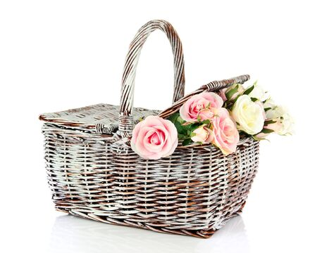 Picnic basket with flowers, isolated on white photo