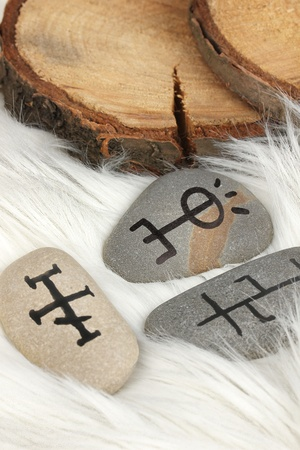 Fortune telling  with symbols on stones on white fur background Stock Photo - 19271633
