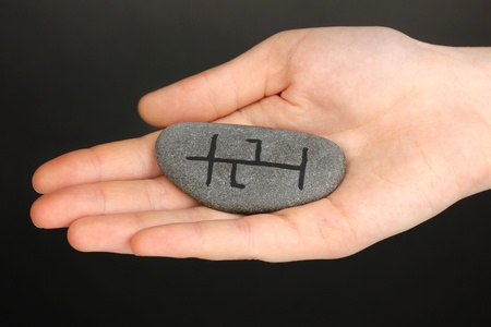 Fortune telling  with symbols on stone in hand on grey background Stock Photo - 19271484