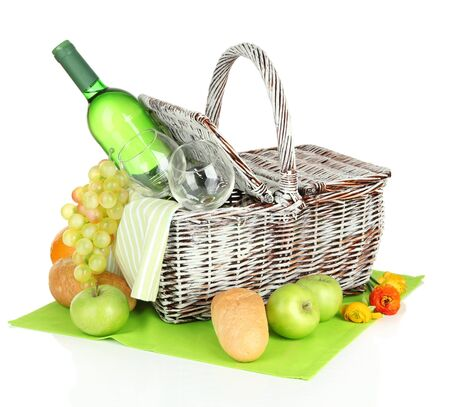 Picnic basket with fruits and bottle of wine, isolated on white photo