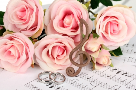 Treble clef, roses and wedding rings on musical background photo