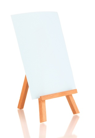 Small easel with sheet of paper isolated on white photo