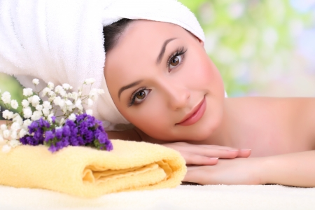 Beautiful young woman with towel on her head on bright background 免版税图像