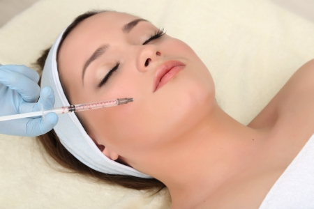 augmentation: Young woman receiving plastic surgery injection on her face close up Stock Photo