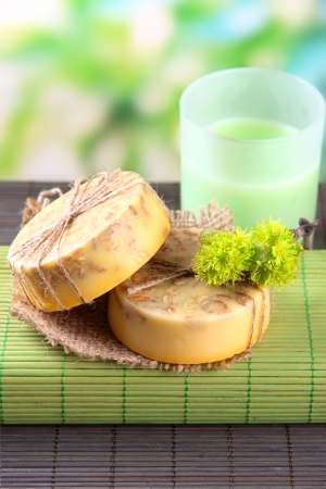 Hand made soap on grey bamboo mat, on green background photo