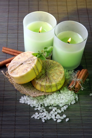 Hand made soap and candles on bamboo mat background photo