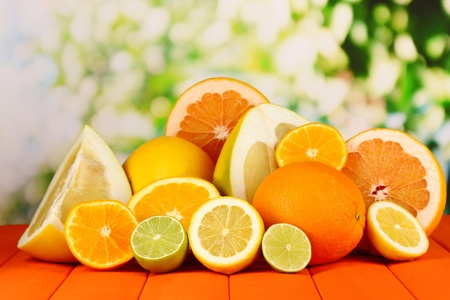 Lots ripe citrus on wooden table on natural background photo