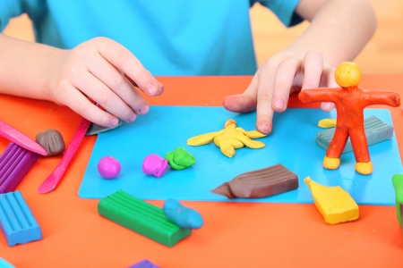 Child moulds from plasticine on table photo