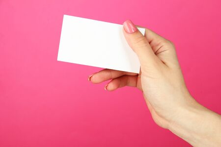 Female hand holding business card, on color background photo
