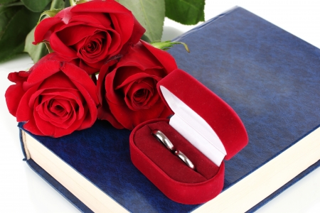 Wedding rings with roses on bible isolated on white photo